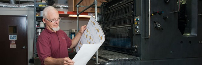 IPC pressman inspects a sheet for quality